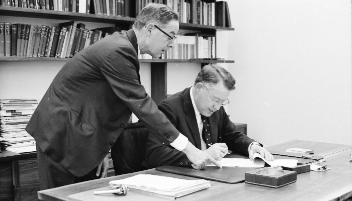 two men sign paperwork