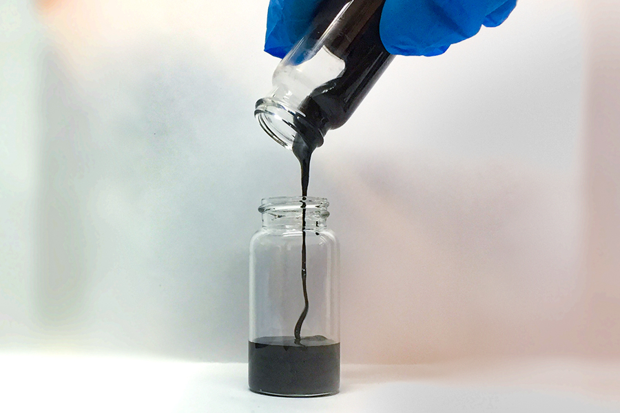 A photo of a researcher pouring a vial of semi-liquid metal anode.