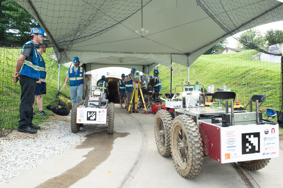 A photo of CMU researchers in a mine with a robot