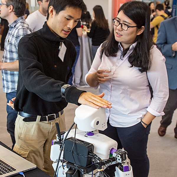 student showing a robot to another student