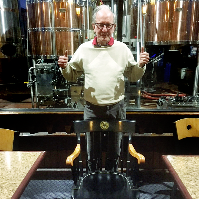 Don Casey, an alumnus, poses with his father Dan's commemorative chair