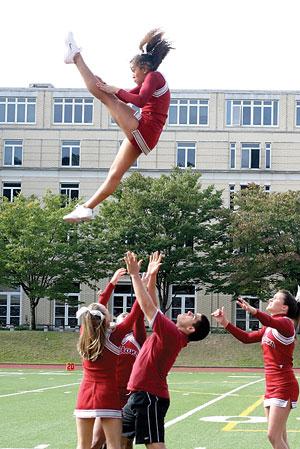 Paul Jasinto catching fellow cheerleader