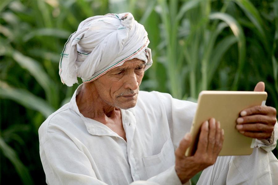 A rural farmer in India looks at an iPad