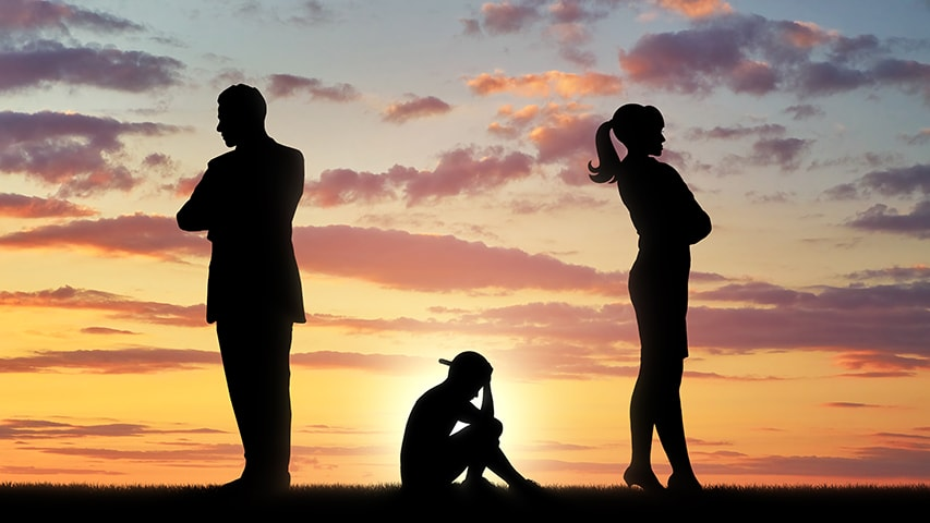 Silhouette image of a sad child sitting between two standing adults not looking at each other