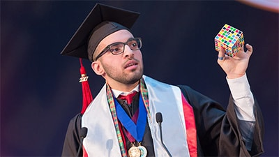 Image of graduation speaker holding a rubiks cube