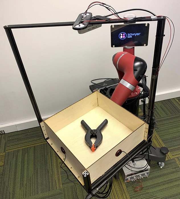 The Tilt Bot has a robotic arm with a wooden tray attached to it. Inside the tray is a metal tool. A camera hangs above the tray.