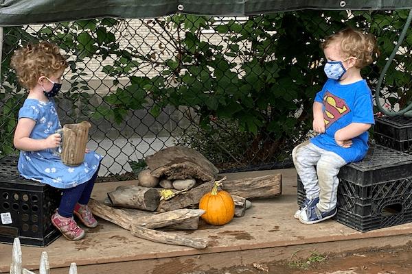 children wearing masks converse outdoors