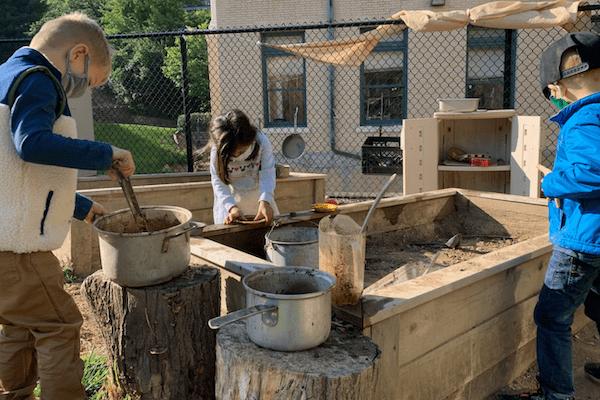 children pretend to cook in the outdoor mud garden