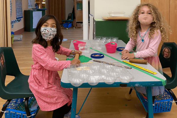children wearing masks play with play dough