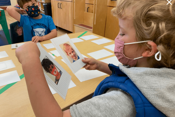 children wearing masks play with face image cards