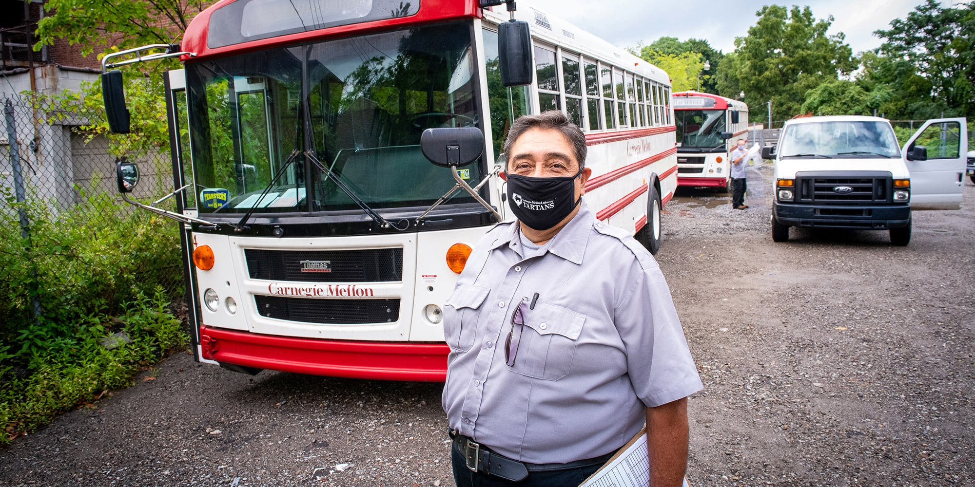 Shuttle driver in front of shuttle wearing a mask